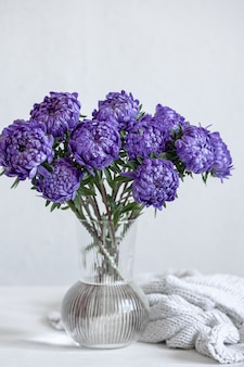 Un bouquet de chrysanthèmes bleus dans un vase en verre sur fond blanc.