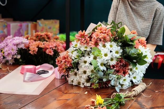 Un bouquet de chrysanthèmes multicolores repose sur une table en bois. le processus de fabrication d'un bouquet de fleurs par un fleuriste.