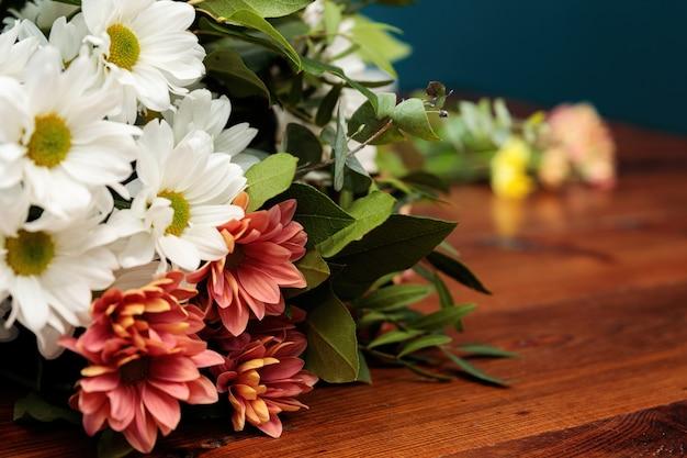 Un bouquet de chrysanthèmes multicolores se trouve sur une table en bois