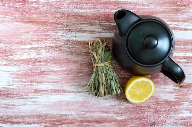 Un bouquet de citronnelle sèche, citron frais, théière. copiez l'espace.