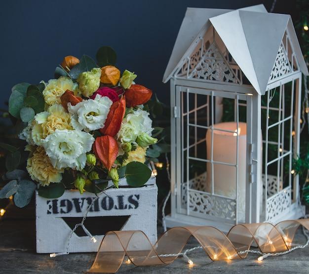 Un bouquet coloré et une bougie allumée dans une cage métallique