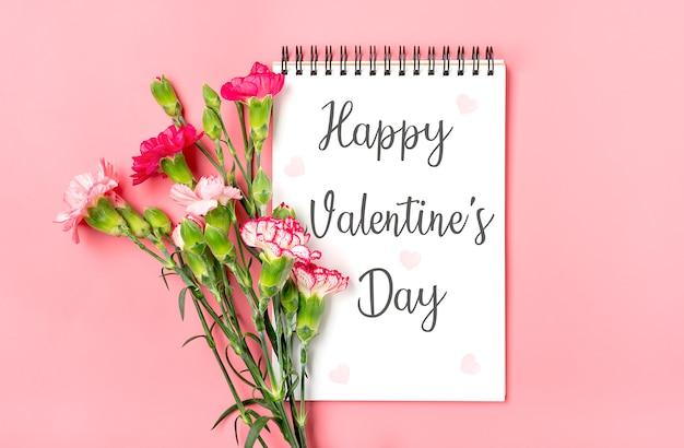 Bouquet coloré de différentes fleurs d'oeillets roses, cahier blanc, stylo sur fond rose