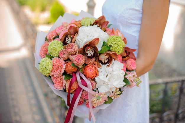 Bouquet coloré entre les mains de la mariée sans visage