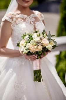 Bouquet dans les mains de la mariée