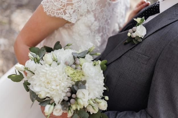 Bouquet délicat avec des chrysanthèmes et boutonnière de marié sur une veste