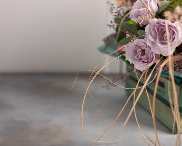Bouquet de délicates roses lilas dans une boîte vintage en bois.