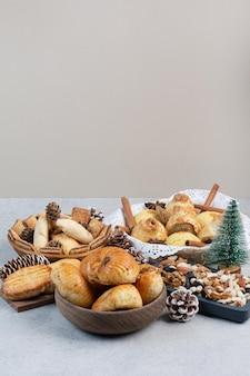 Bouquet de divers biscuits, noix et pommes de pin dans des bols. photo de haute qualité