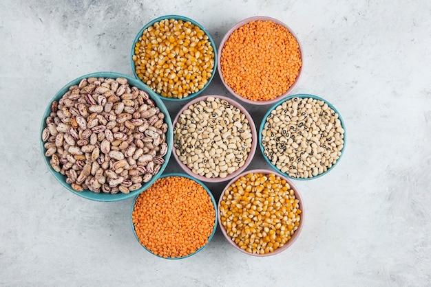 Bouquet de divers haricots non cuits, maïs et lentilles rouges dans des bols.