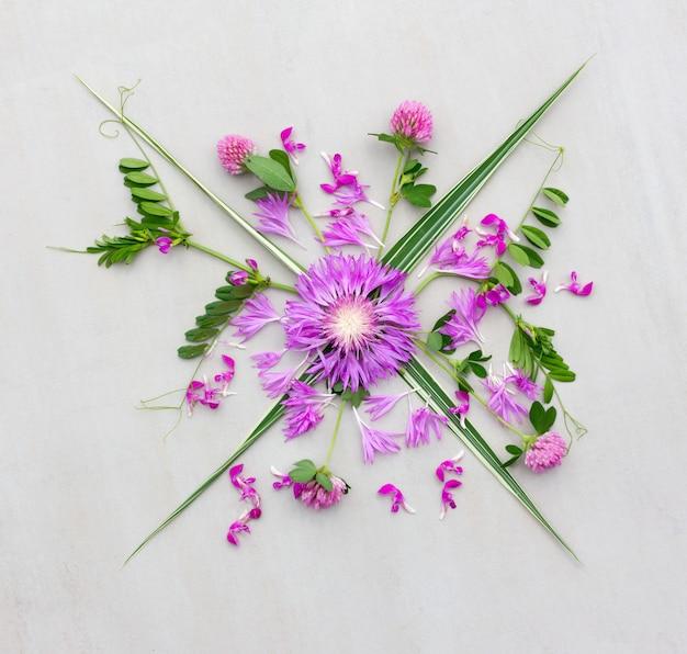 Un bouquet de diverses fleurs violettes avec des feuilles vertes sur fond gris. lay plat, vue de dessus