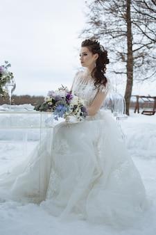 Bouquet entre les mains de la mariée, assise sur une chaise. photographie de mariage d'hiver