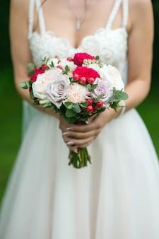 Bouquet entre les mains de la mariée de roses rouges claires et lumineuses