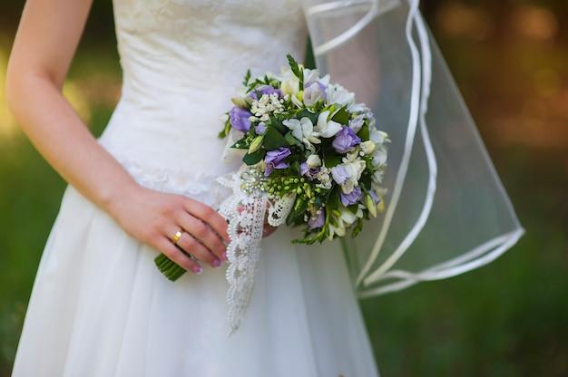 Bouquet entre les mains de la mariée