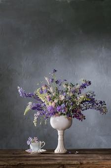 Bouquet d'été aux couleurs bleues et violettes sur mur sombre