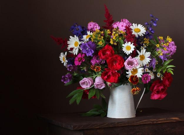 Bouquet d'été dans un pot: roses, marguerites, phlox, cloches et autres fleurs du jardin
