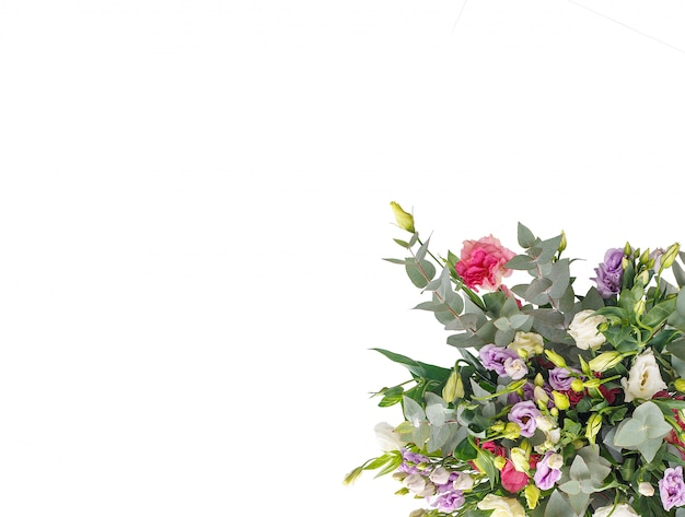 Bouquet d'eustomess et d'eucalyptus sur un mur blanc