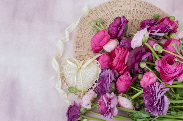 Un bouquet d'éventail de ranunculus, coeur de dentelle, ruban de dentelle