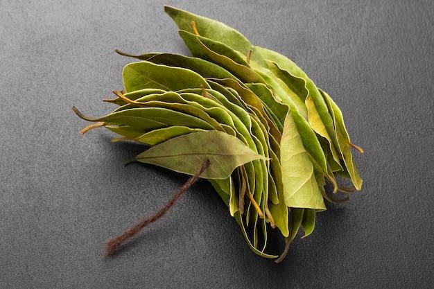 Bouquet de feuilles de laurier sur fond noir. épices pour les plats. espace de copie