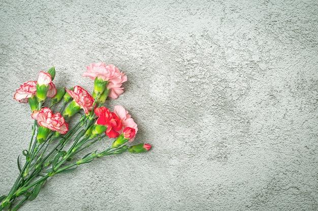 Bouquet de fleur oeillet rose sur fond de béton gris