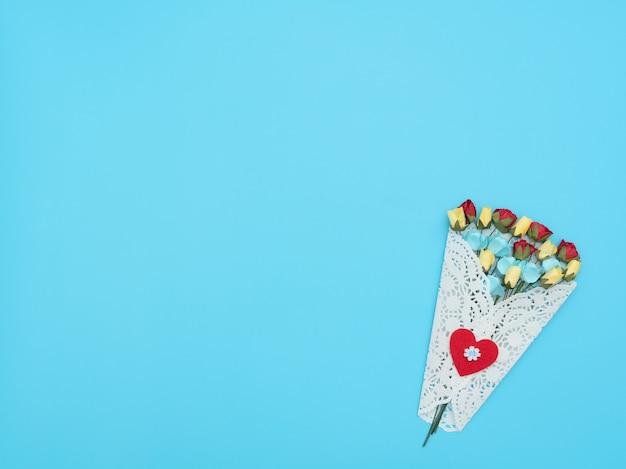 Le bouquet de fleurs artisanales enveloppé dans un paquet de dentelle blanche sur fond bleu