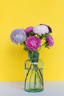 Bouquet de fleurs d'asters coloré dans un vase en verre.