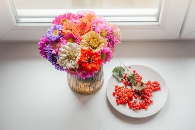 Un bouquet de fleurs d'automne avec des baies de rose guelder sur la vue de dessus du rebord de la fenêtre