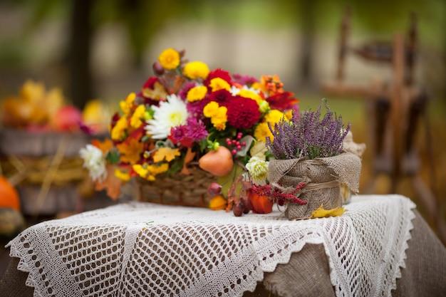 Bouquet de fleurs d'automne dans le panier sur la table dans un style rustique. temps de l'automne.