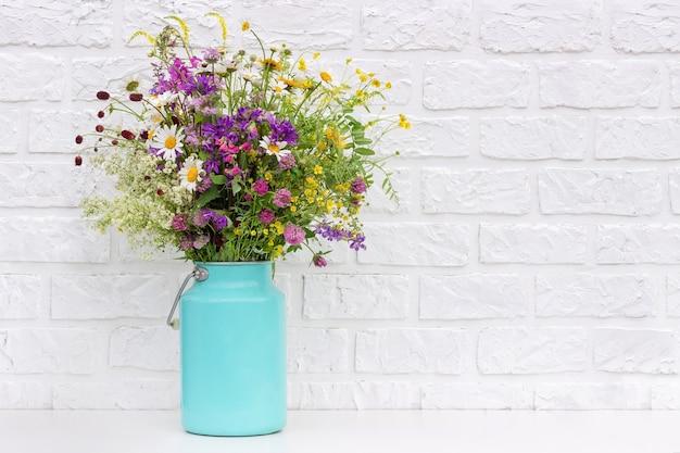 Bouquet de fleurs aux couleurs vives dans un vase de boîte de conserve sur fond de mur de briques blanches. modèle de carte postale. concept journée de la femme, fête des mères, bonjour l'été ou bonjour le printemps.