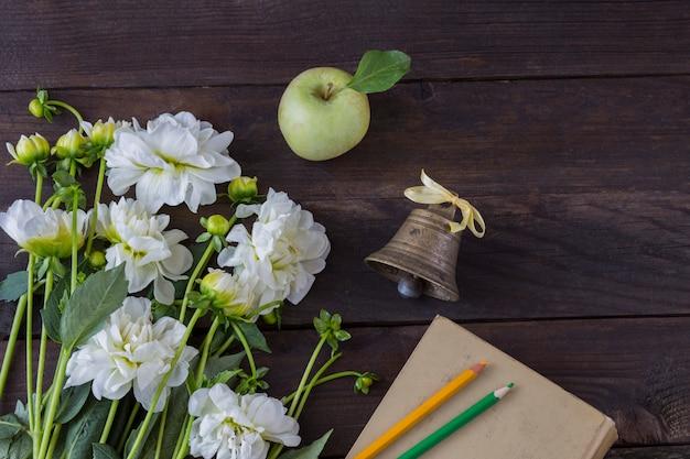 Un bouquet de fleurs blanches, un livre, des crayons (jaune et vert), une vieille clochette et une pomme verte