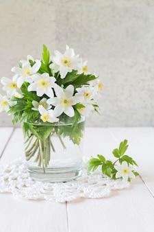 Bouquet de fleurs blanches printanières en verre sur une table en bois