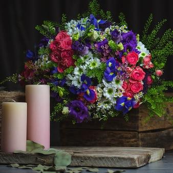 Bouquet de fleurs et bougies roses sur un espace en bois rustique.