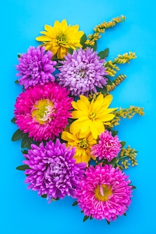 Un bouquet de fleurs, carte postale florale bleue avec des asters violets et des marguerites jaunes sauvages.