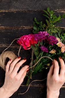 Bouquet de fleurs dans une main féminine sur une table en bois noire