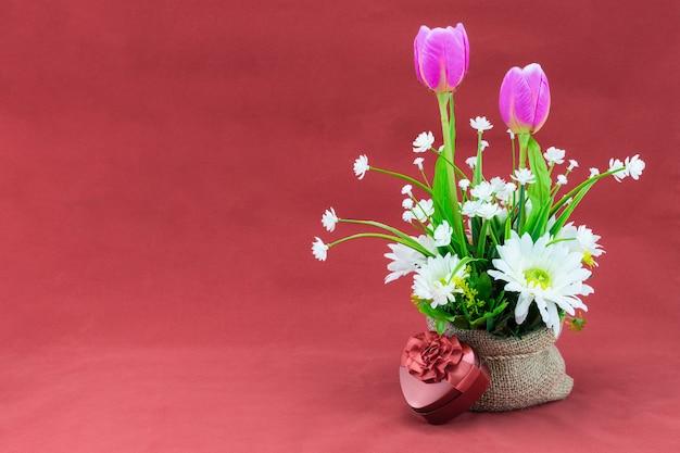 Bouquet de fleurs dans un sac et boîte cadeau coeur de lecture, isolé sur rose gris.