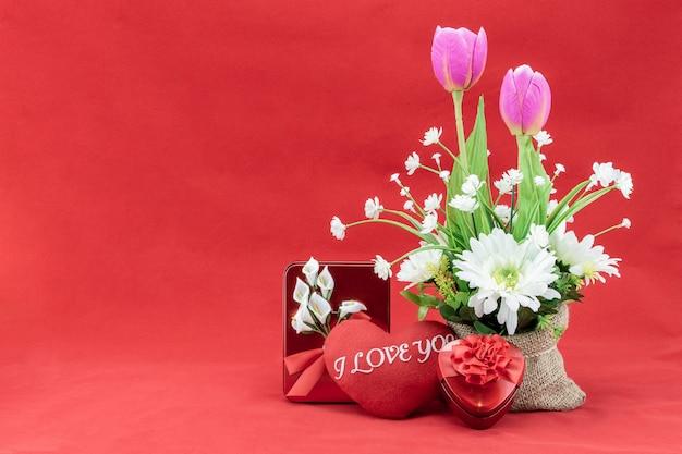 Bouquet de fleurs dans un sac sur fond rouge pour l'amour ou le concept de la saint-valentin