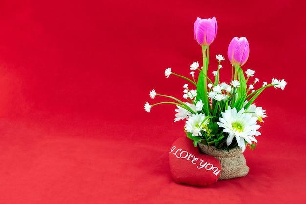 Bouquet de fleurs dans un sac et petit oreiller en forme de coeur sur fond rouge pour l'amour ou le concept de la saint-valentin