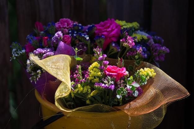 Un bouquet de fleurs dans un seau en plastique. fleurs naturelles
