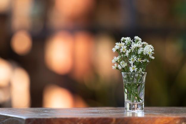 Bouquet de fleurs dans un vase sur une table en bois. avec jardin en arrière plan.