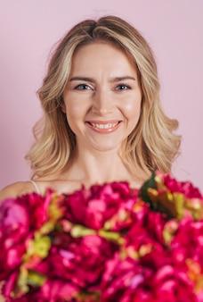 Bouquet de fleurs défocalisé devant une jeune femme souriante sur fond rose