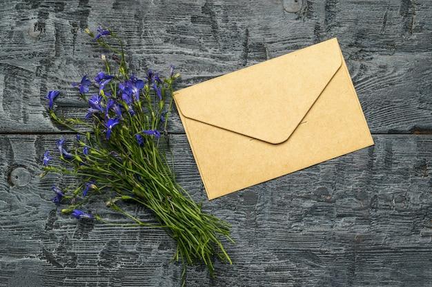 Un bouquet de fleurs et une enveloppe postale en papier sur une table en bois. mise à plat.