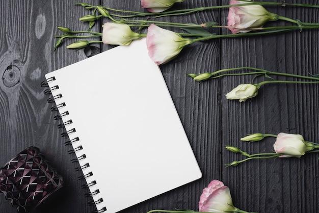 Bouquet de fleurs d'eustoma violet sur le cahier à spirale vierge
