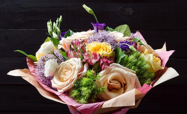 Un bouquet de fleurs sur un fond en bois sombre. bouquet de roses.