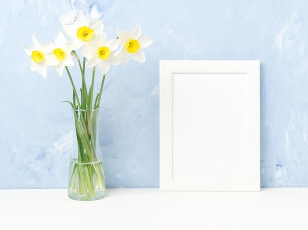 Bouquet de fleurs fraîches, cadre blanc sur table, en face du mur de béton texturé bleu.