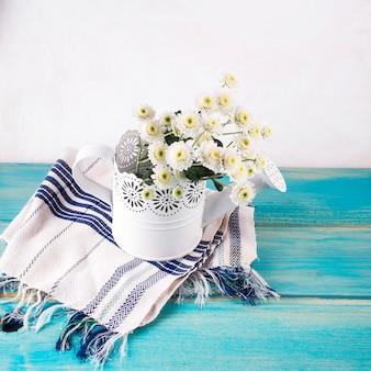 Bouquet de fleurs fraîches dans un arrosoir ornemental sur une serviette