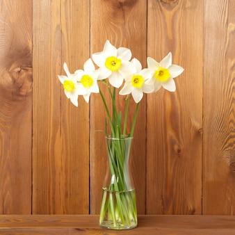 Bouquet de fleurs fraîches, jonquilles dans un vase au milieu d'une table en bois