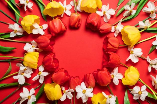 Bouquet de fleurs fraîches et lumineuses cadre sur fond rouge avec espace de copie