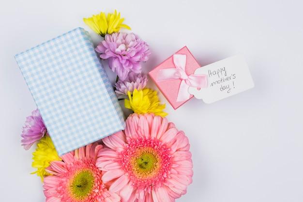Bouquet de fleurs fraîches près de tag avec des mots et des boîtes à cadeaux