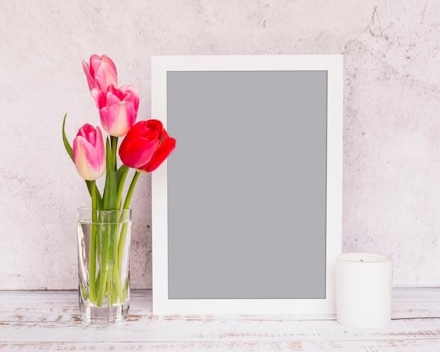 Bouquet de fleurs fraîches sur les tiges dans un vase près du cadre et de la bougie