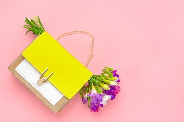 Bouquet de fleurs de freesia violet, sac à main en cuir couleurs jaune, beige, blanc sur fond rose lay plat