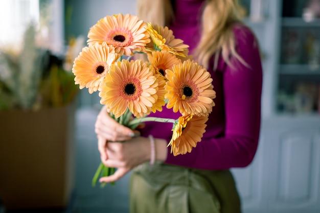 Bouquet de fleurs de gerbera lumineux à la main.