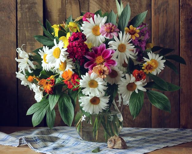 Bouquet de fleurs de jardin dans un pichet en verre et un coquillage devant un fond en bois.